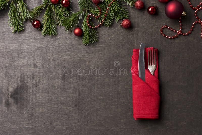 与叉子的假日在红色餐巾的服务和刀子在木背景 免版税库存图片