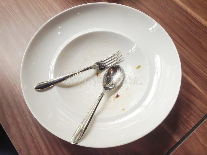与叉子的白色盘和匙子在吃以后 免版税库存照片