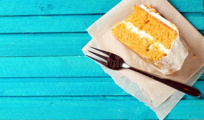 与叉子的胡萝卜糕在一张蓝色木桌上 免版税图库摄影