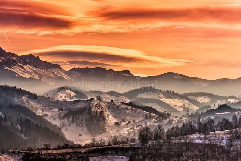与双突透镜的云彩的美丽的橙色日落天空在冬天山风景Pestera, Moeciu 免版税库存照片