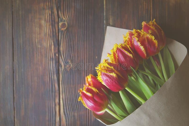 与双颜色郁金香的时髦的葡萄酒花束构成在黑褐色木桌上 在纸包裹的双色的花 免版税库存照片