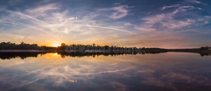 与反射、天空蔚蓝和黄色阳光的美好的风景在日出 免版税库存照片