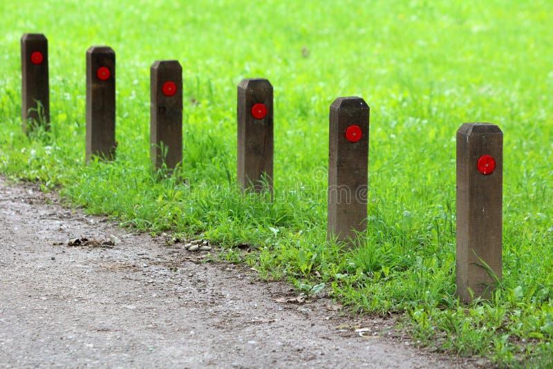 与反射性红色小点的多根小木杆在石渣道路旁边连续投入了围拢与未割减的草在地方公园 免版税库存图片