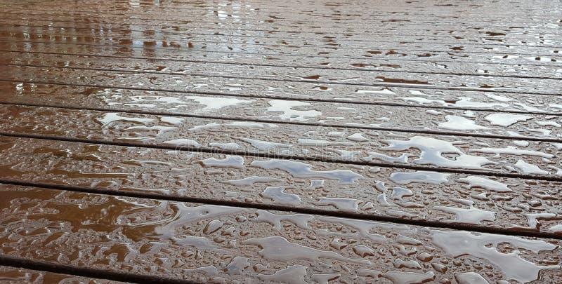 与反射的串珠的水在黑褐色木头甲板 免版税库存图片
