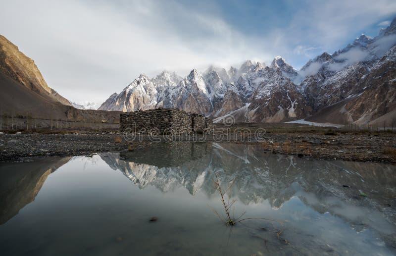 与反射的山风景在水 单独石小屋立场在喀喇昆仑山脉范围在巴基斯坦 库存照片