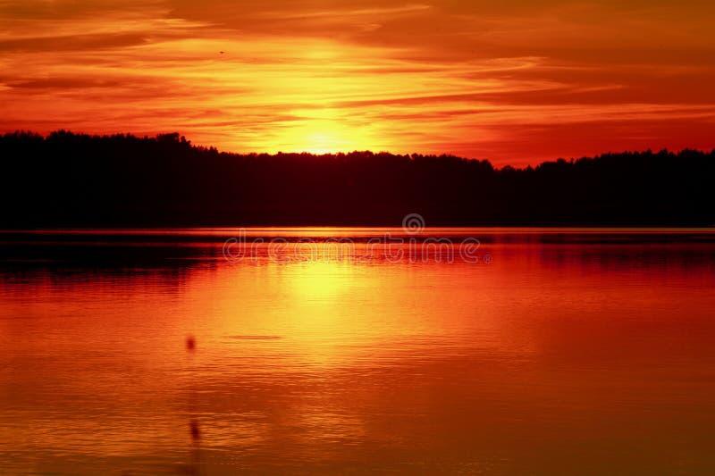 与反射的红色日落在湖 库存照片