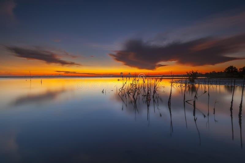 与反射的美丽的灼烧的天空在夏天日出/日落期间 免版税库存图片