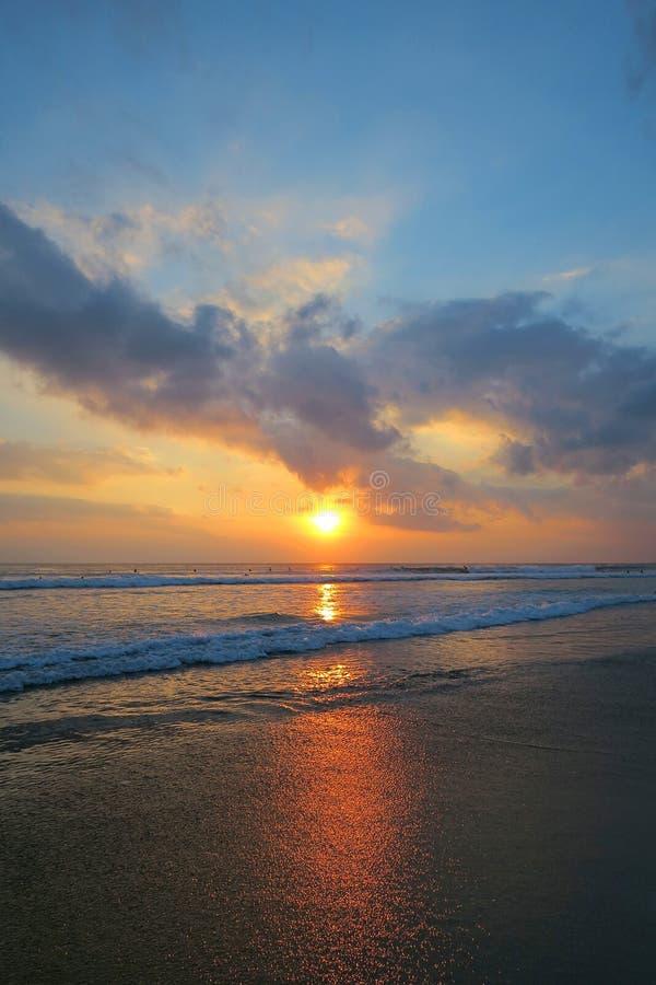 与反射的美好的颜色库塔海滩日落在湿沙子,巴厘岛,印度尼西亚 免版税图库摄影