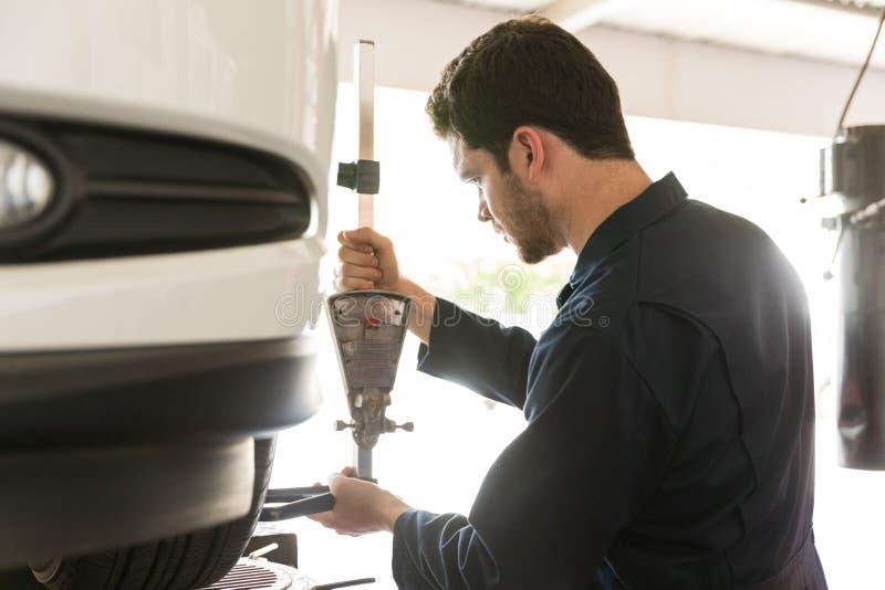 与反挠度适配器的技工审查的轮胎对准线 免版税图库摄影
