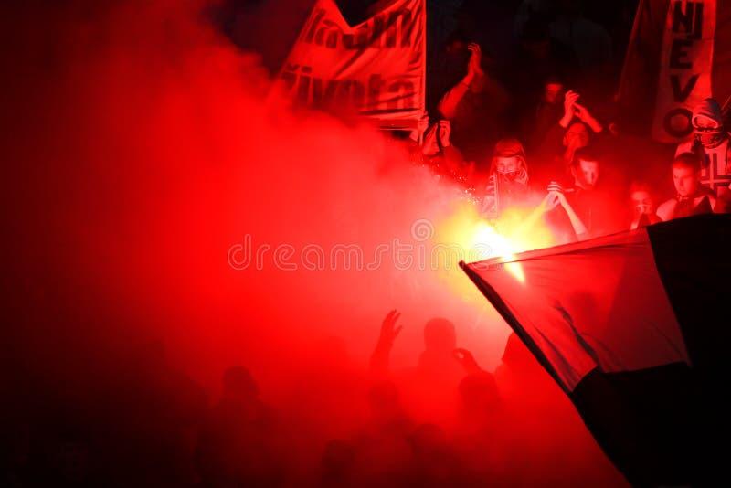 与发亮的足球迷在体育场的火炬 库存图片