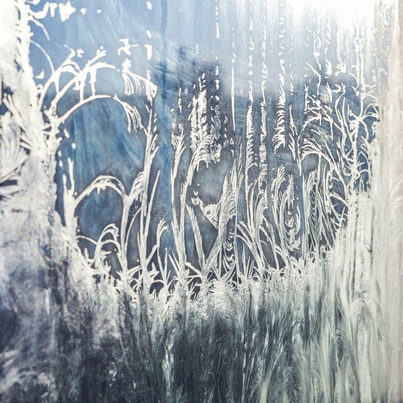 与发光的冰霜样式纹理的冻冬天窗口 免版税库存图片