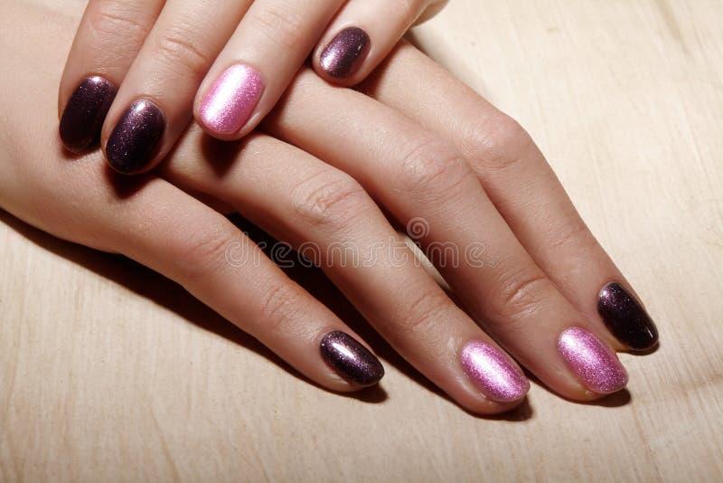 与发光的指甲油的被修剪的钉子 与明亮nailpolish的修指甲 时尚与发光的胶凝体亮漆的艺术修指甲 库存照片