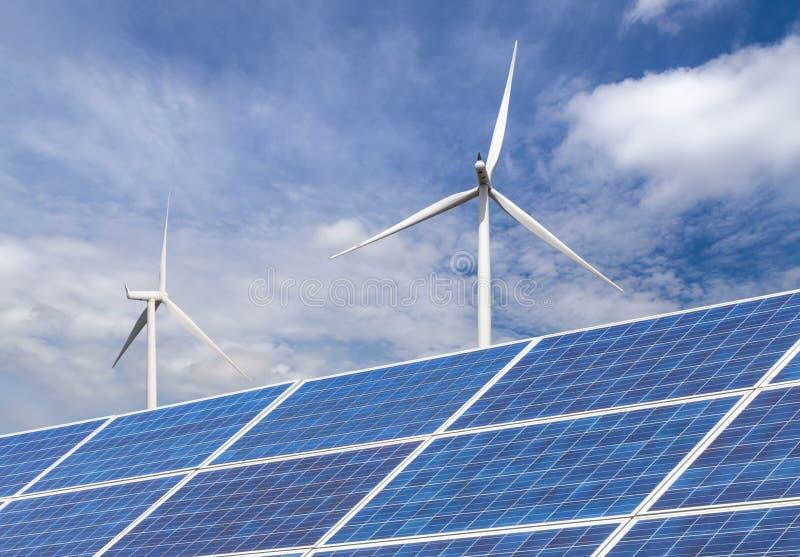 与发在杂种能源厂系统驻地的风轮机的太阳能电池电在蓝天背景 免版税库存图片