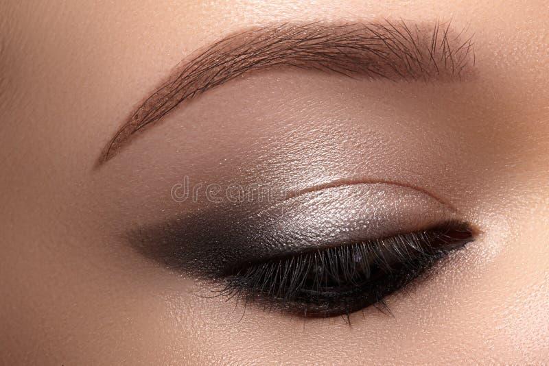 与发烟性猫眼构成的美丽的宏观眼睛 化妆用品和构成 时尚脸特写镜头与划线员,眼影膏的 免版税图库摄影