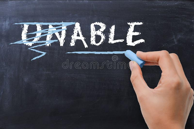 """与变换词""""unable†的妇女的正面想法的概念对在黑板的词""""able† 库存图片"""