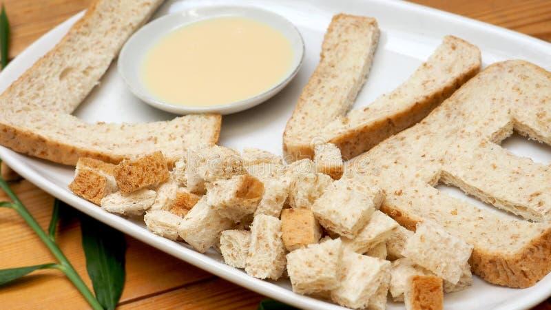 与变甜的浓缩牛奶creat早餐的全麦面包 免版税图库摄影