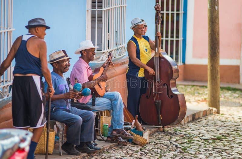 与古典音乐的殖民地加勒比镇街道艺术家音乐家带和大厦在特立尼达,古巴,美国 免版税库存照片