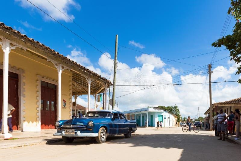 与古巴人民和美国蓝色克莱斯勒经典汽车的街道生活视图在圣克拉拉古巴- Serie古巴报告文学 库存照片
