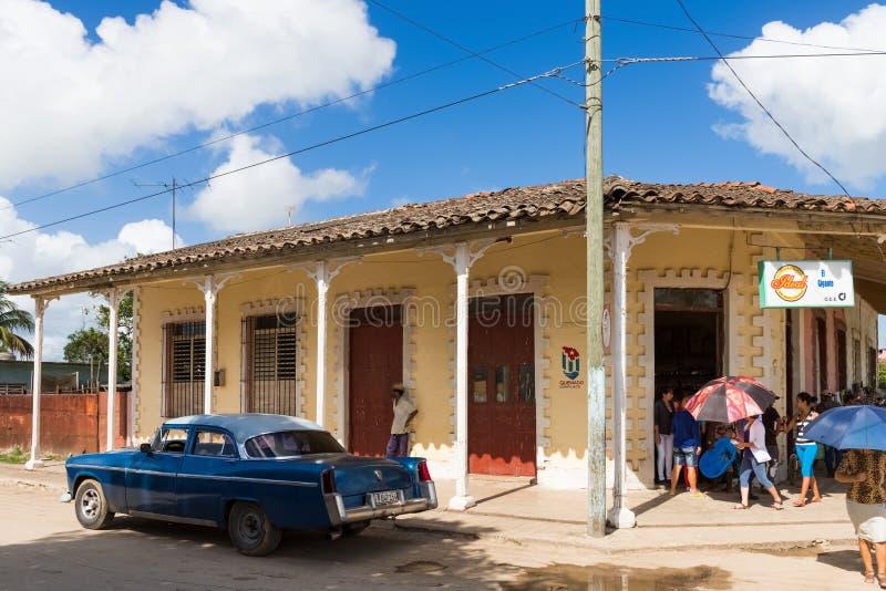 与古巴人民和美国蓝色克莱斯勒经典汽车的街道生活视图在圣克拉拉古巴- Serie古巴报告文学 图库摄影