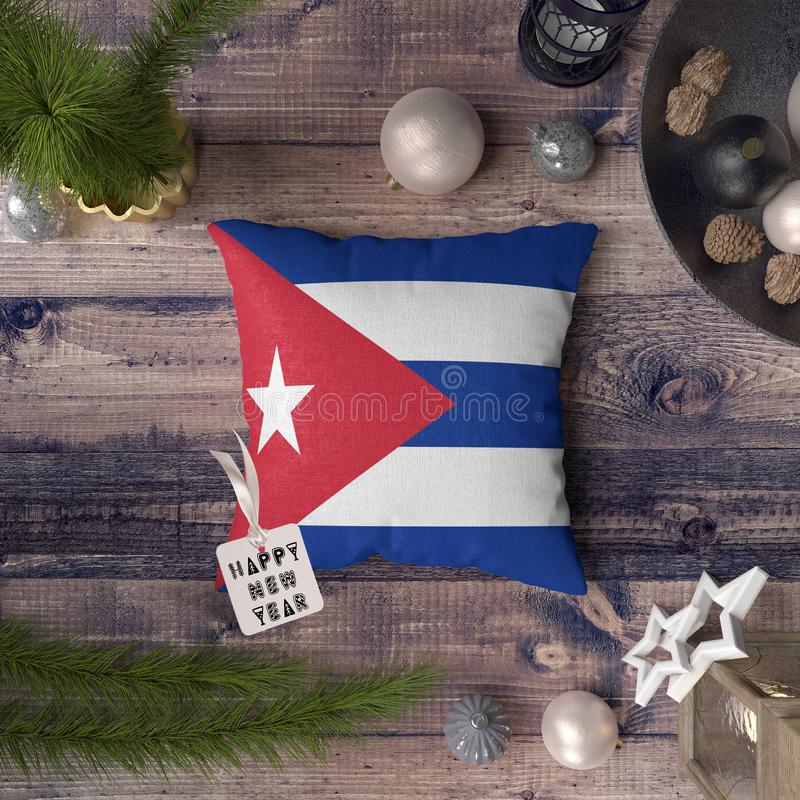 与古巴旗子的新年快乐标记在枕头 在木桌上的圣诞装饰概念与可爱的对象 图库摄影