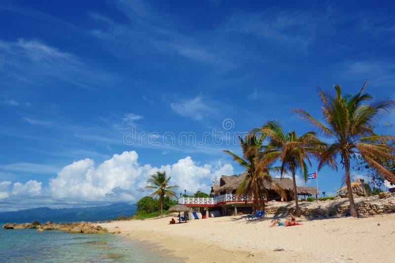 与古巴棕榈树包围的旗子和一个传统古巴房子, Playa肘,特立尼达,古巴, Caribbea的热带沙滩 库存照片