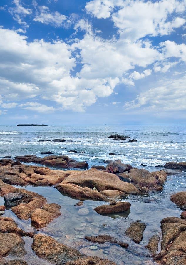 与古怪的形状的岩石的平静的海滨, 免版税库存图片