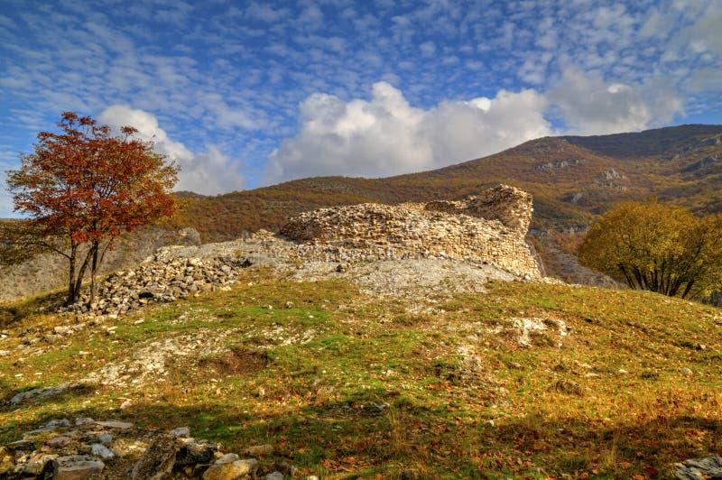 与古老堡垒和五颜六色的秋天树废墟的山风景  库存图片