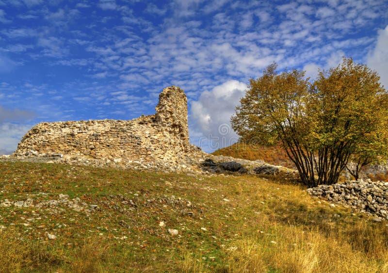 与古老堡垒和五颜六色的秋天树废墟的山风景  免版税库存图片