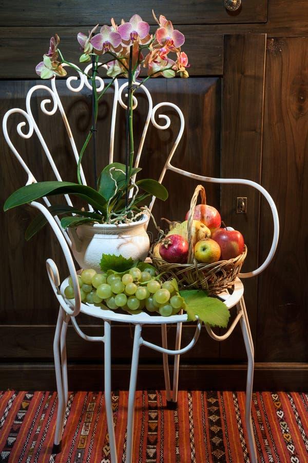 与古色古香的椅子、花和果子的静物画 库存照片