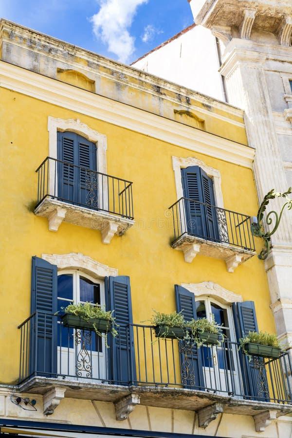 与古色古香的窗口的典型的黄色大厦在维罗纳 免版税库存照片