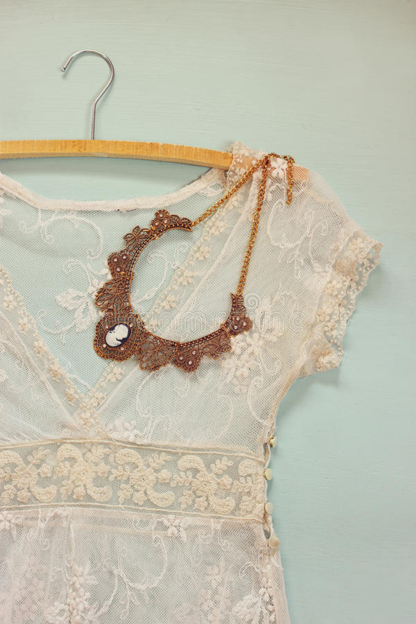 与古色古香的项链的葡萄酒白色钩针编织鞋带上面在木背景 图库摄影