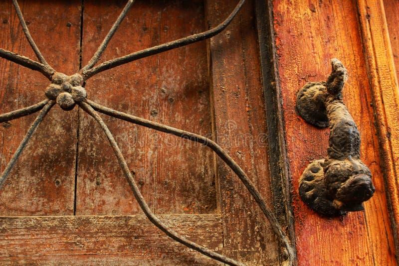 与古铜色敲门人的老木门 免版税库存照片