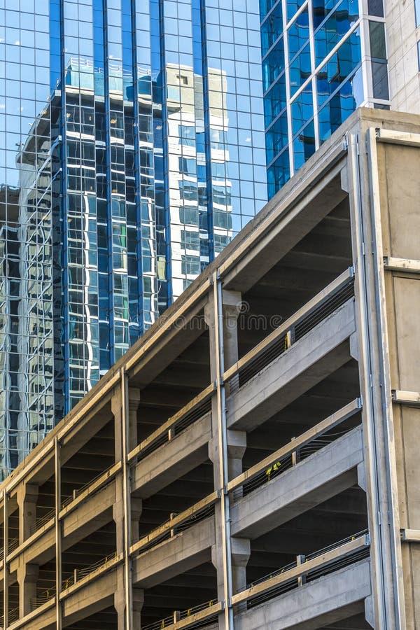 与另一个大厦的反射的一个蓝色玻璃大厦 新的停车库 免版税库存照片