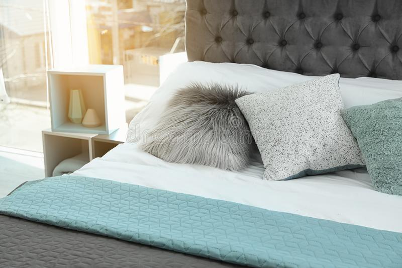 与另外枕头和格子花呢披肩的舒适床 内部装饰的想法 库存图片