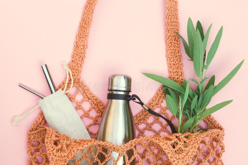 与可再用的水瓶和金属秸杆的网兜,不去绿色和使用用途塑料 免版税库存照片