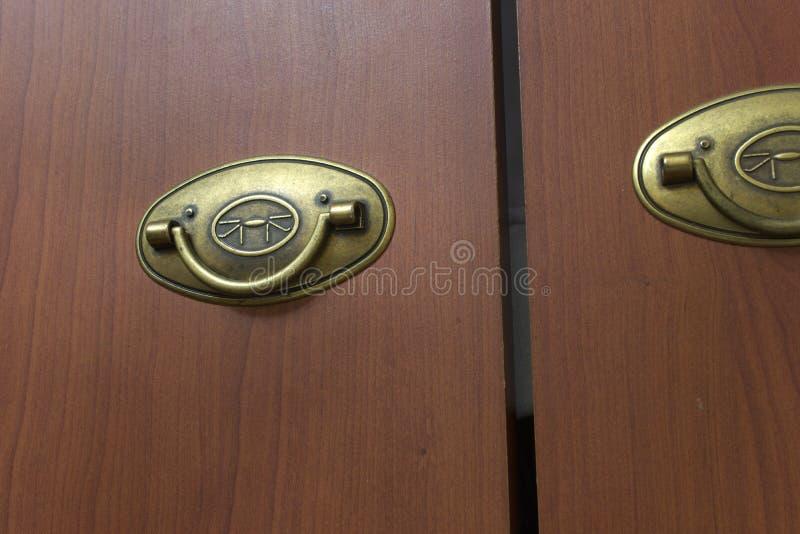 与可折叠的拉扯把柄的衣橱门 人工老化的黄铜 免版税库存照片