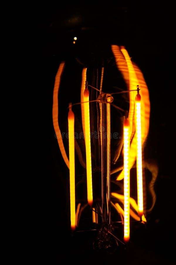与可看见的发光的导线的被修补的经典白炽爱迪生电灯泡夜 库存照片