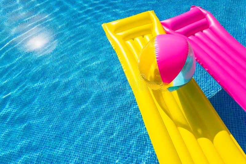 与可膨胀的球的黄色和桃红色气垫在游泳池 免版税库存照片