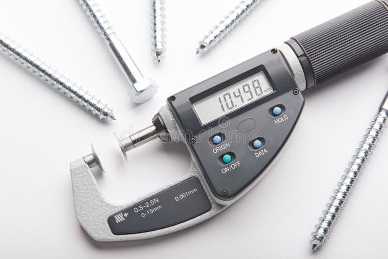 与可调整的压力测量的数字式测微表与在白色背景的钢螺丝 图库摄影
