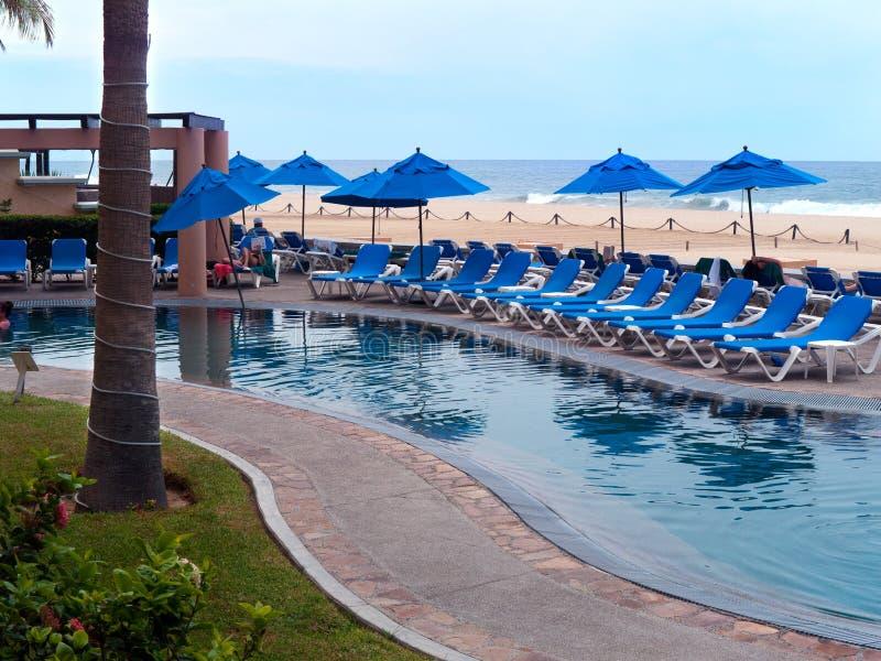 与可躺式椅蓝色伞和海滩的水池 免版税库存照片