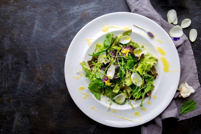 与可食的花和microgreens的健康莴苣芝麻菜沙拉在白色板材,黑暗的背景 顶视图 免版税库存图片