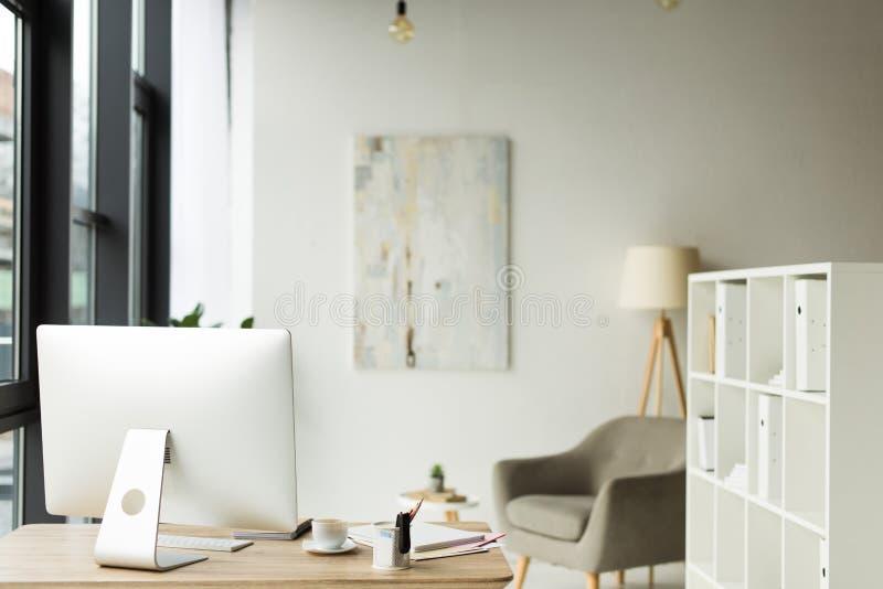 与台式计算机和纸的现代办公室内部在桌上 库存图片