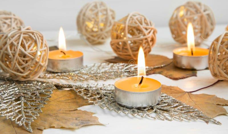 与叶子和光装饰的秋天蜡烛 免版税图库摄影