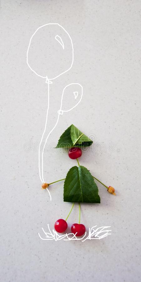 与叶子和樱桃,有a的一个人的滑稽的构成 免版税图库摄影