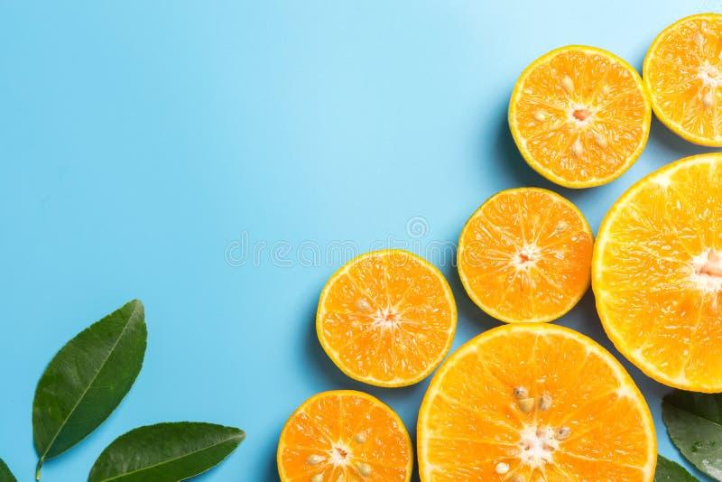 与叶子的切的橙色果子在蓝色背景 免版税库存照片