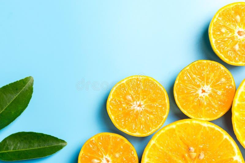 与叶子的切的橙色果子在蓝色背景 库存照片