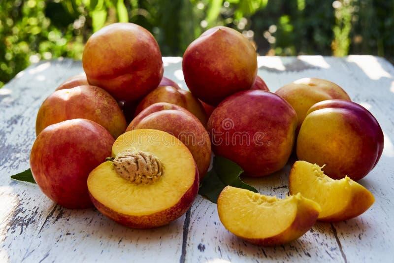 与叶子的成熟桃子在以绿色叶子为背景的老木桌上在庭院里 免版税库存图片
