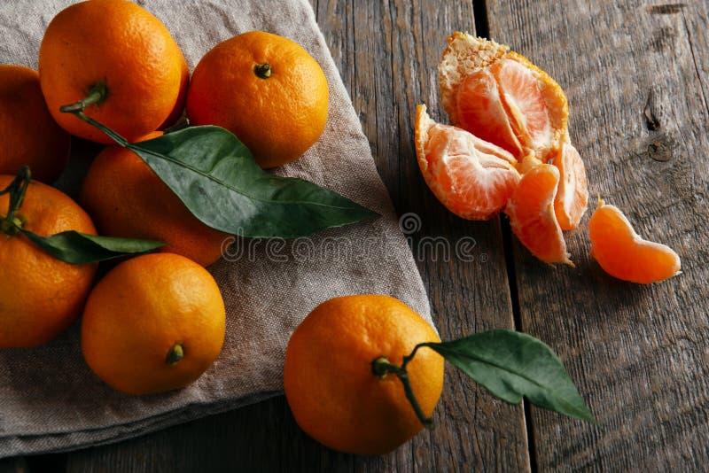 与叶子的成熟蜜桔在木桌上 库存图片