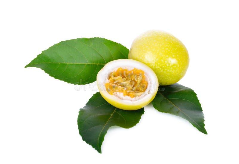 与叶子的整体和半裁减新鲜的黄色西番莲果在白色 免版税库存照片