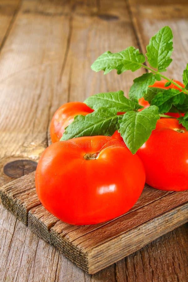 与叶子的新鲜的蕃茄在一张老木桌上 免版税库存照片